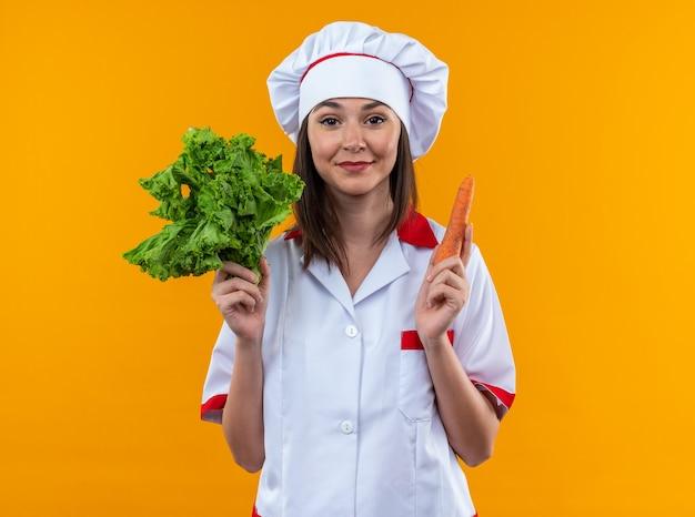 Blije jonge vrouwelijke kok die een uniform van de chef-kok draagt met salade met wortel geïsoleerd op een oranje muur