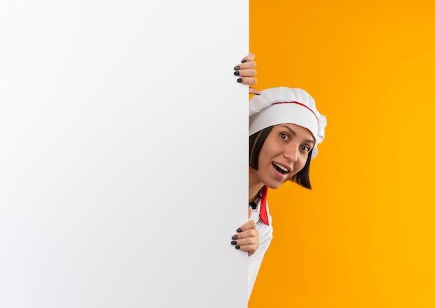 Blije jonge vrouwelijke kok die in eenvormige chef-kok voorzijde van achter witte muur bekijkt die op oranje wordt geïsoleerd