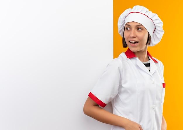 Blije jonge vrouwelijke kok in eenvormige chef-kok die op witte muur leunt en kant bekijkt die op sinaasappel wordt geïsoleerd