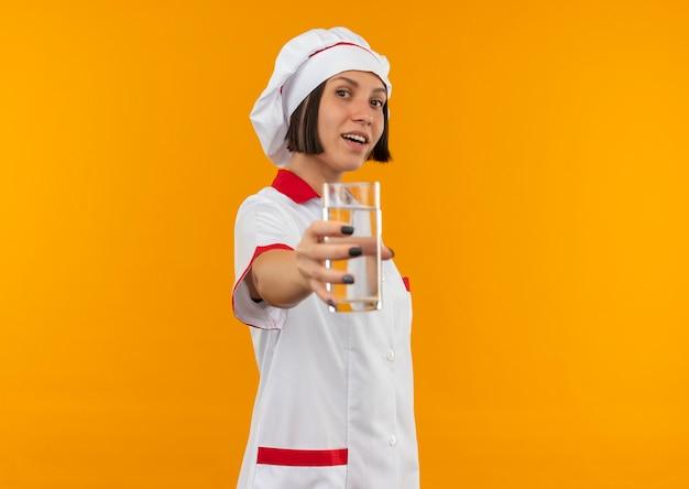 Blije jonge vrouwelijke kok in eenvormige chef-kok die uit glas water uitrekt dat op sinaasappel wordt geïsoleerd
