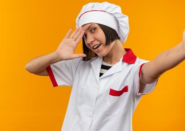Blije jonge vrouwelijke kok in eenvormige chef-kok die uit hand uitrekt en hallo gesturing op sinaasappel wordt geïsoleerd