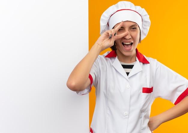 Blije jonge vrouwelijke kok in eenvormige chef-kok die zich voor witte muur bevindt die hand op taille doet die vredesteken doet dat op oranje wordt geïsoleerd