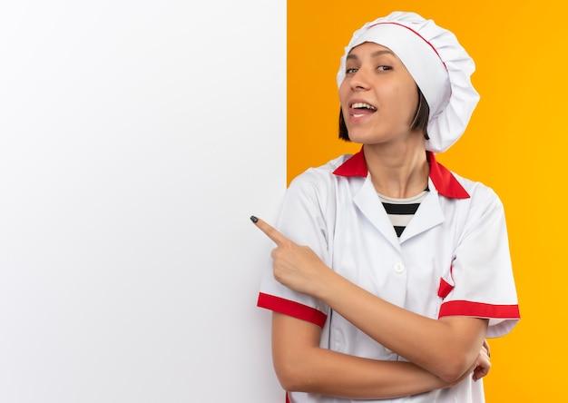Blije jonge vrouwelijke kok in eenvormige chef-kok die zich voor witte muur bevindt die tong toont en op muur richt die op sinaasappel wordt geïsoleerd