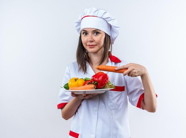 Blije jonge vrouwelijke kok in uniform van de chef-kok met groenten op plaat geïsoleerd op een witte muur