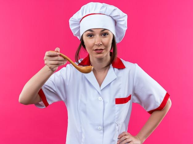 Blije jonge vrouwelijke kok met een uniform van de chef-kok die een lepel vasthoudt die de hand op de heup legt, geïsoleerd op een roze achtergrond