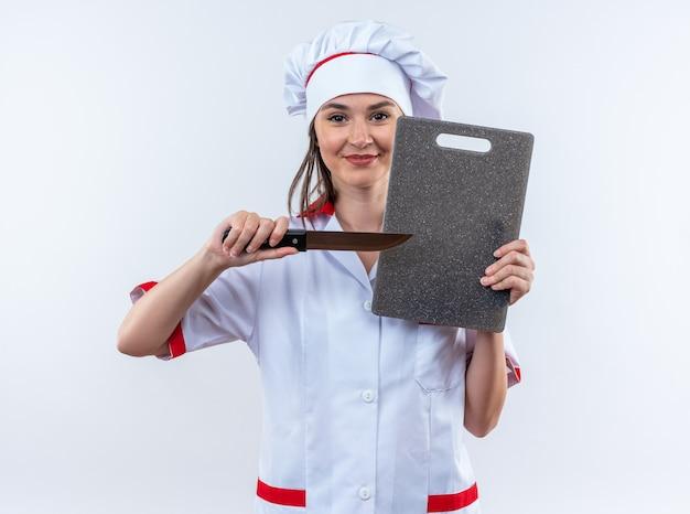 Blije jonge vrouwelijke kok met een uniform van de chef-kok die mes vasthoudt met een snijplank geïsoleerd op een witte muur