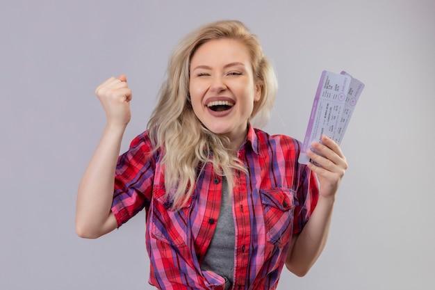 Blije jonge vrouwelijke reiziger die de rode kaartjes van de overhemdsholding op geïsoleerde witte muur draagt