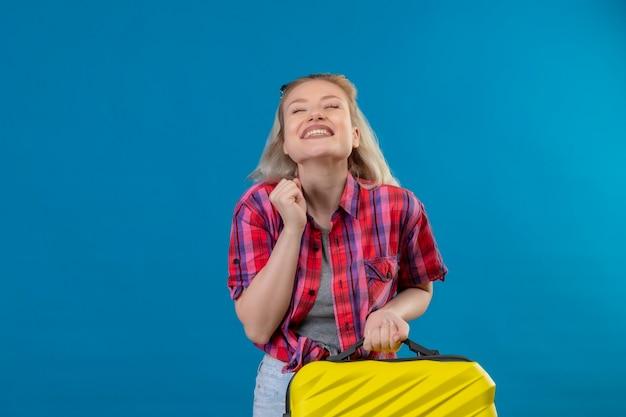 Blije jonge vrouwelijke reiziger die de rode koffer van de overhemdsholding op geïsoleerde blauwe muur draagt