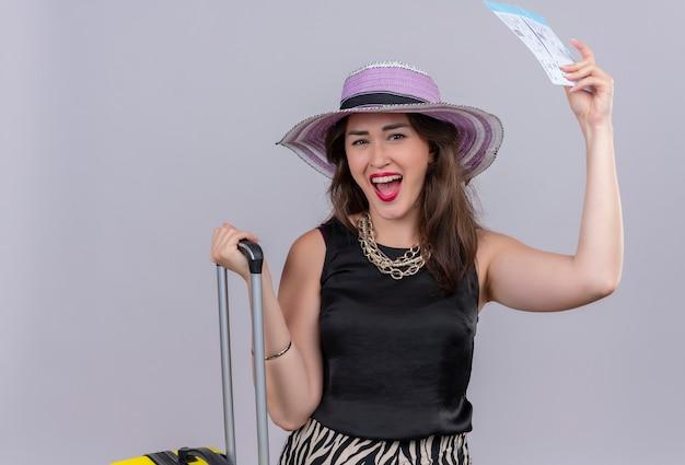 Blije jonge vrouwelijke reiziger die de zwarte koffer en kaartjes van de onderhemdholding op witte muur draagt
