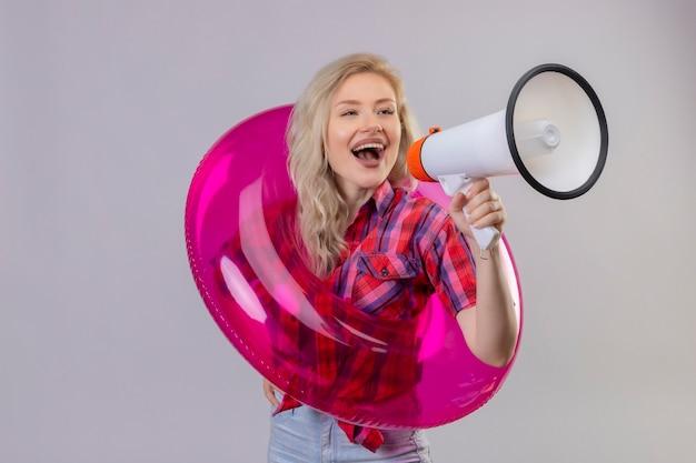 Blije jonge vrouwelijke reiziger die een rood overhemd in opblaasbare ring draagt, spreekt door luidsprekers op geïsoleerde witte muur