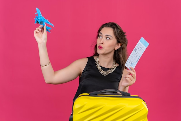 Blije jonge vrouwelijke reiziger die het zwarte kaartje van de onderhemdholding draagt en een stuk speelgoed vliegtuig op rode muur speelt