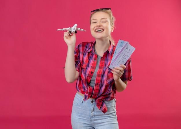 Blije jonge vrouwelijke reiziger die rood overhemd en een bril op haar hoofd draagt ?? die stuk speelgoed plan met kaartjes op geïsoleerde roze muur houdt