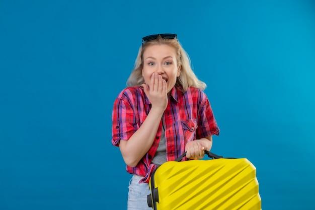 Blije jonge vrouwelijke reiziger die rood overhemd en glazen op hoofd draagt ?? die koffer behandelde mond op geïsoleerde blauwe muur houdt