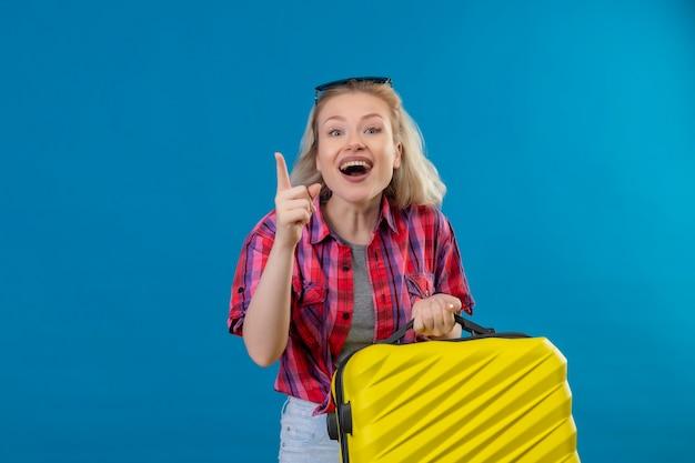 Blije jonge vrouwelijke reiziger die rood overhemd en glazen op hoofd draagt ?? die koffer wijst naar kant op geïsoleerde blauwe muur