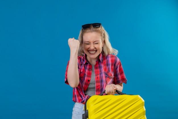 Blije jonge vrouwelijke reiziger die rood overhemd en glazen op hoofdholding koffer draagt op geïsoleerde blauwe muur