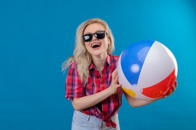 Blije jonge vrouwelijke reiziger die rood overhemd in glazen draagt die opblaasbare bal op geïsoleerde blauwe muur houdt