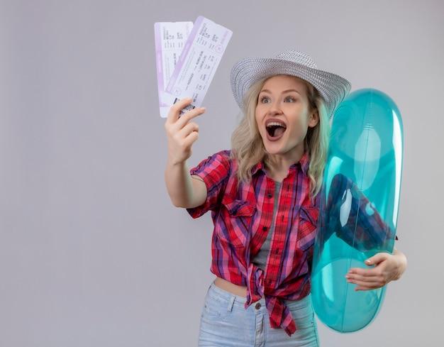 Blije jonge vrouwelijke reiziger die rood overhemd in hoed draagt die opblaasbare ring en kaartjes op geïsoleerde witte muur houdt