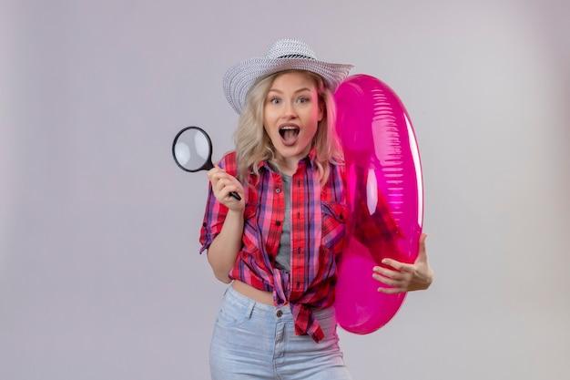 Blije jonge vrouwelijke reiziger die rood overhemd in hoed draagt die opblaasbare ring en meer magnifier op geïsoleerde witte muur houdt
