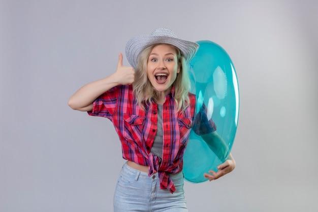 Blije jonge vrouwelijke reiziger die rood overhemd in hoed draagt die opblaasbare ring haar duim tegen geïsoleerde witte muur houdt