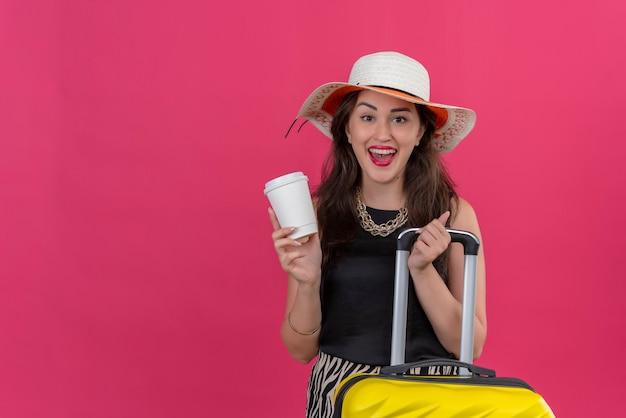 Blije jonge vrouwelijke reiziger die zwart onderhemd in de kop van de hoedenholding van koffie op rode muur draagt