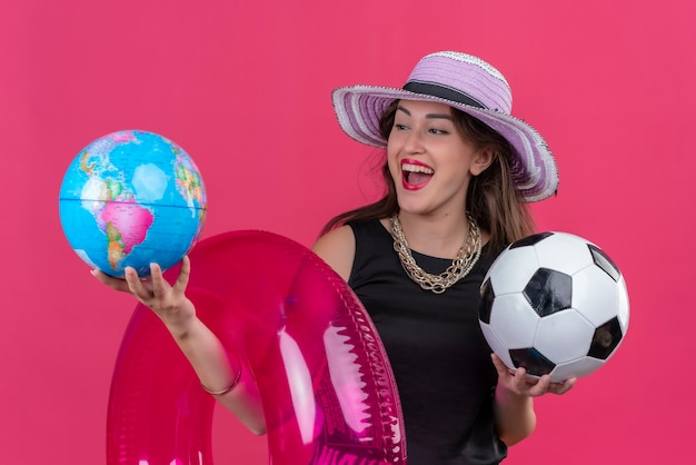 Blije jonge vrouwelijke reiziger die zwart onderhemd in hoed draagt die opblaasbare cirkel en bal met bol op rode muur houdt