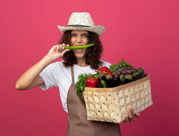 Blije jonge vrouwelijke tuinman in eenvormig die het tuinieren hoed dragen die plantaardige mand houden en peper proberen die op roze wordt geïsoleerd