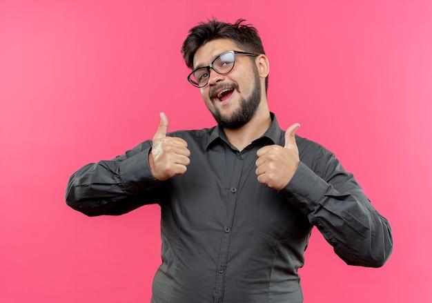 Blije jonge zakenman die glazen draagt zijn duimen omhoog geïsoleerd op roze muur