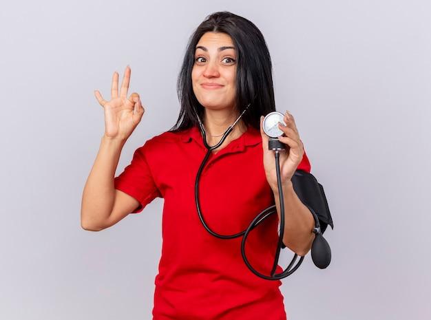 Blije jonge zieke vrouw die een stethoscoop draagt en kijkt naar de voorkant die haar druk meet met een bloeddrukmeter die ok teken doet dat op witte muur wordt geïsoleerd