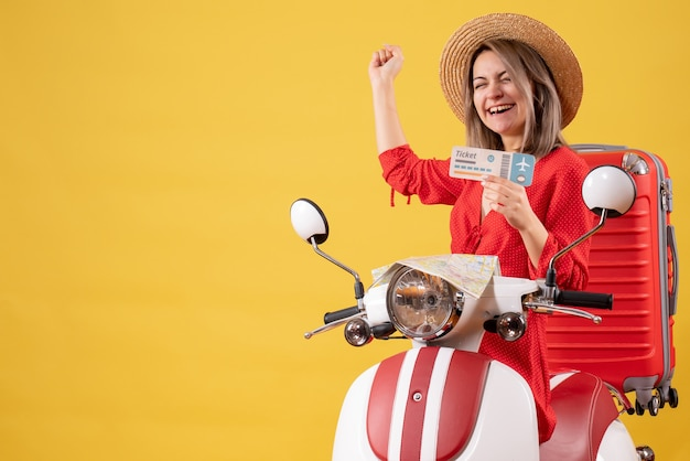 Blije jongedame in rode jurk met kaartje op bromfiets