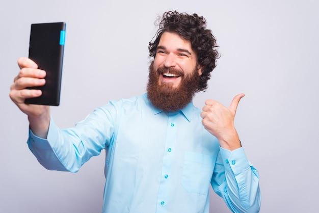 Blije jongeman houdt een duim omhoog en neemt een selfie met stootkussen bij een grijze muur