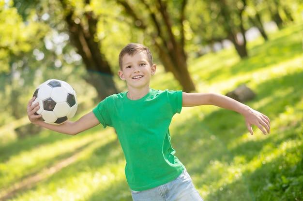 Blije jongen die met bal in park loopt