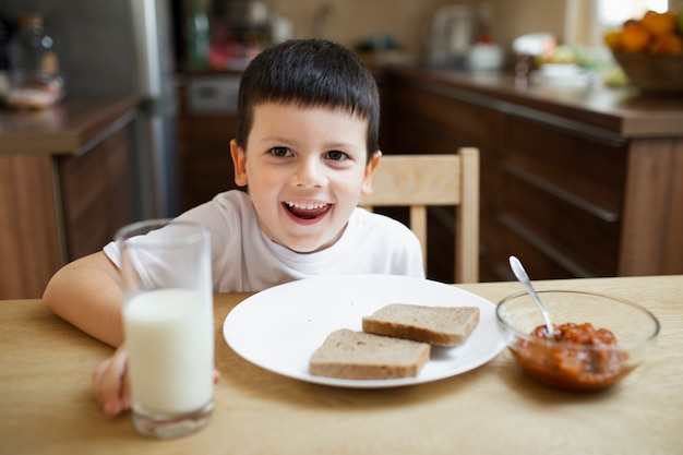 Blije jongen die rond terwijl het eten speelt