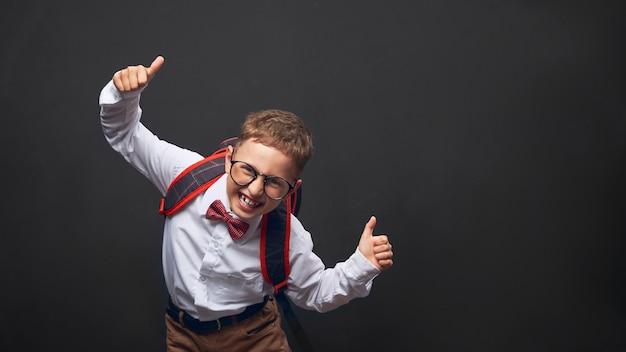 Blije jongen op een zwarte achtergrond met een aktentas achter zijn schouders