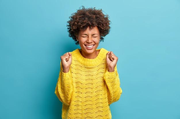 Blije, jubelende vrouw juicht en balt haar vuisten na het ontvangen van goed nieuws ziet er dolgelukkig uit om te slagen, gekleed in gebreide gele trui