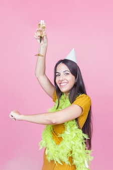 Blije kaukasische vrouw die met opgeheven glas champagne tegen roze achtergrond danst