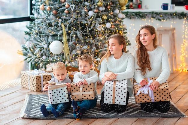 Blije kinderen bij de kerstboom met de cadeautjes