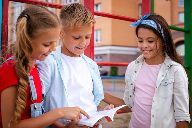 Blije kinderen die een notitieboekje bekijken