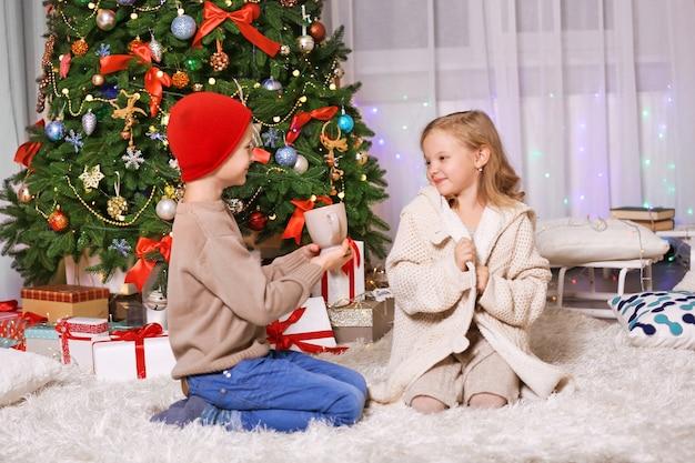 Blije kinderen met beker als cadeau in de versierde kerstkamer