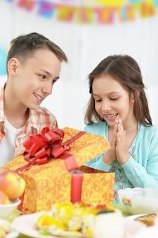 Blije kinderen met taart en cadeau op verjaardagsfeestje