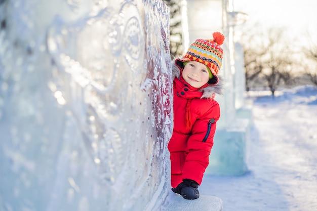 Blije kleine jongen op de achtergrond van het ijssculptuur. leuk winterplezier in de sneeuw