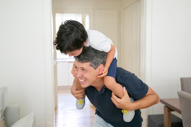 Blije kleine jongen zittend op de schouders van de vader en lachen.