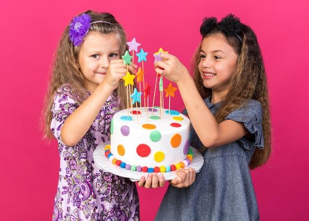 Blije kleine mooie meisjes die verjaardagstaart bij elkaar houden geïsoleerd op roze muur met kopieerruimte