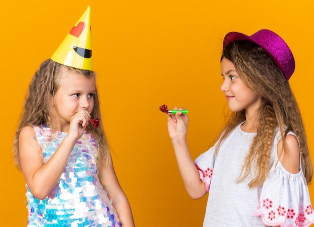 Blije kleine mooie meisjes met feestmuts met feestfluitjes en kijken naar elkaar geïsoleerd op oranje muur met kopieerruimte