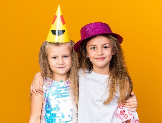 Blije kleine mooie meisjes met feestmutsen die elkaar omhelzen en geïsoleerd op een oranje muur met kopieerruimte