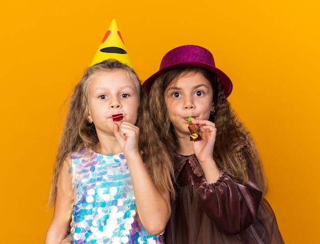 Blije kleine mooie meisjes met feestmutsen die feestfluitjes blazen geïsoleerd op een oranje muur met kopieerruimte