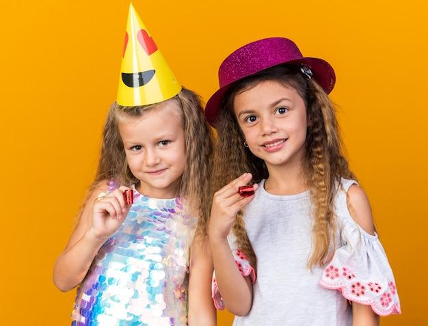Blije kleine mooie meisjes met feestmutsen met feestfluitjes geïsoleerd op een oranje muur met kopieerruimte