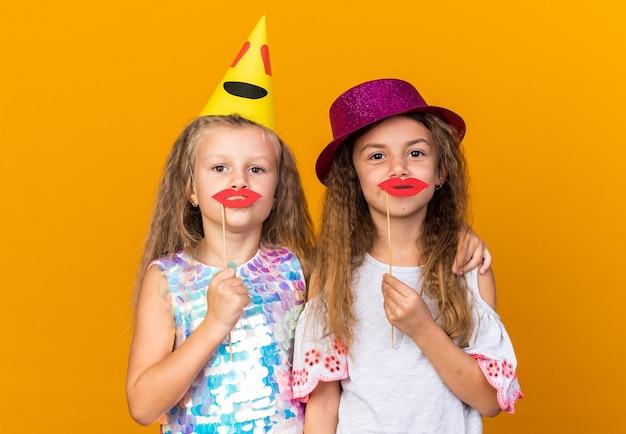 Blije kleine mooie meisjes met feestmutsen met valse lippen op stokjes geïsoleerd op een oranje muur met kopieerruimte