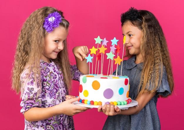 Blije kleine mooie meisjes met verjaardagstaart geïsoleerd op roze muur met kopieerruimte