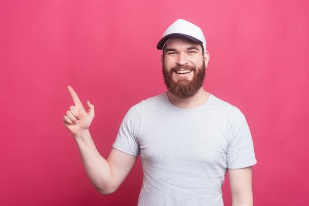 Blije knappe mens die op copyspace over roze muur richt
