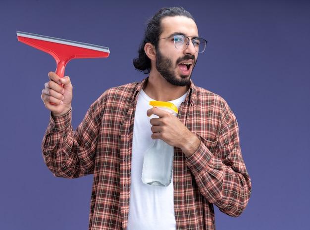 Blije knipperde jonge knappe schoonmaakster die t-shirt draagt die zwabberhoofd met sproeifles houdt die op blauwe muur wordt geïsoleerd